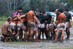Rugby match in muddy field for article on back pain in the UK